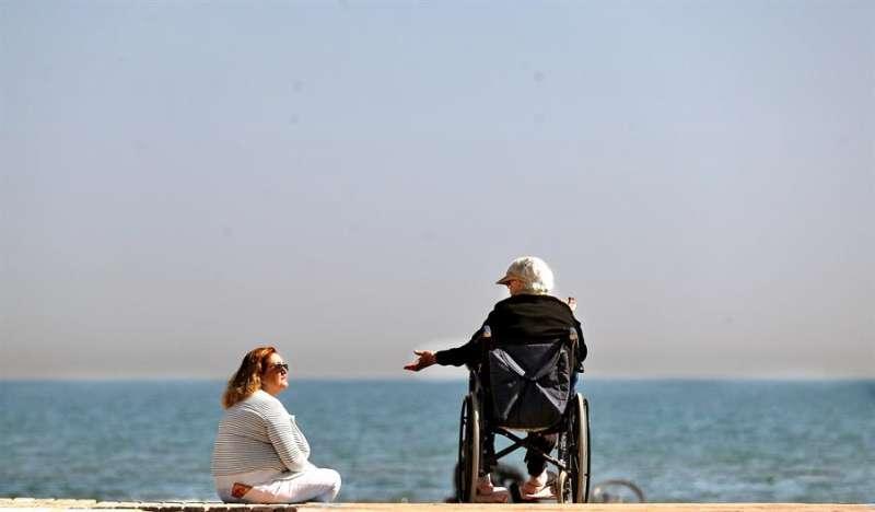 Dos mujeres conversan a orillas del mar en la playa de la Malvarrosa de Valencia. EFE
