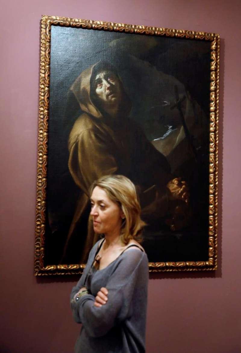 Una mujer pasa ante uno de los dos cuadros del siglo XVII restaurados por la Catedral de Valencia, cuya autoría se atribuye a Jerónimo Jacinto Espinosa (en la imagen). EFE