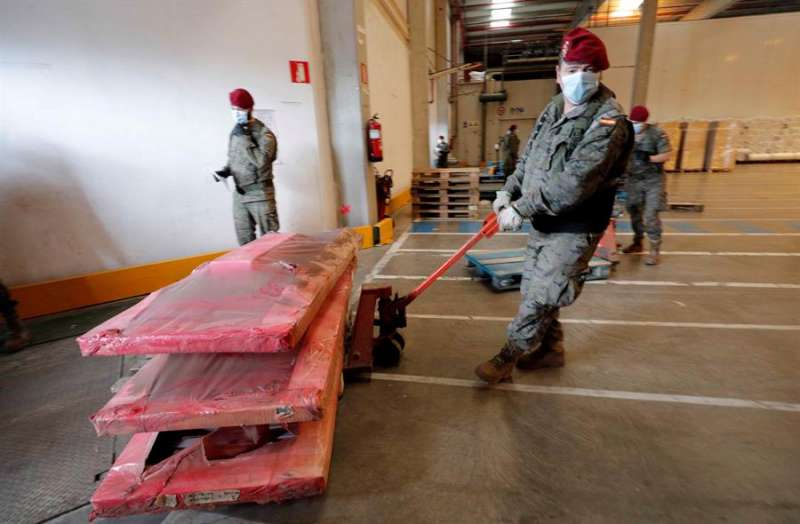 Varios soldados trabajan en el almacenamiento de 386 camas geriátricas para proceder a su posterior distribución según las necesidades. EFE/Juan Carlos Cárdenas