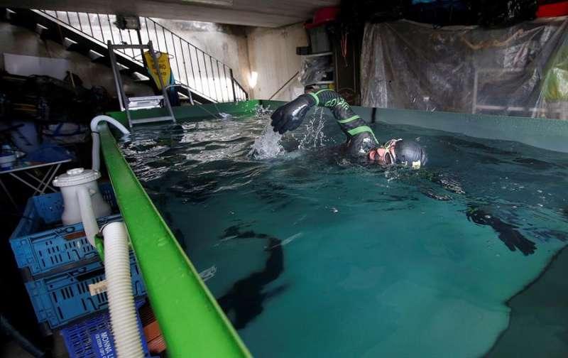 El triatleta Isidro Benavent ha desarrollado el ingenio y ha tenido en cuenta cada detalle, en el garaje de su domicilio, para usar un contenedor como piscina para de esta forma poder completar la parte de la natación en el entrenamiento que practica durante el confinamiento. EFE/Miguel Ángel Polo