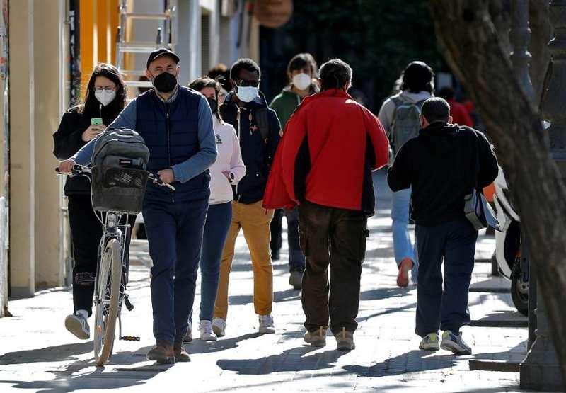 Varias personas protegidas con mascarillas por la ciudad de València, en una imagen de este lunes. EFE