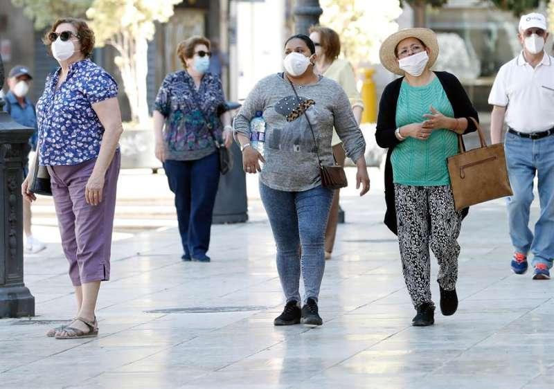 Varias personas protegidas con mascarilla en Valencia, este miércoles, sexagésimo séptimo día del estado de alarma. EFE/ Juan Carlos Cárdenas