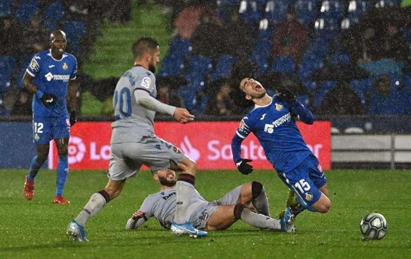 El centrocampista del Getafe CF Marc Cucurella (d) cae tras la entrada de Rubén Rochina (c), del Levante UD. EFE/FERNANDO VILLAR/Archivo