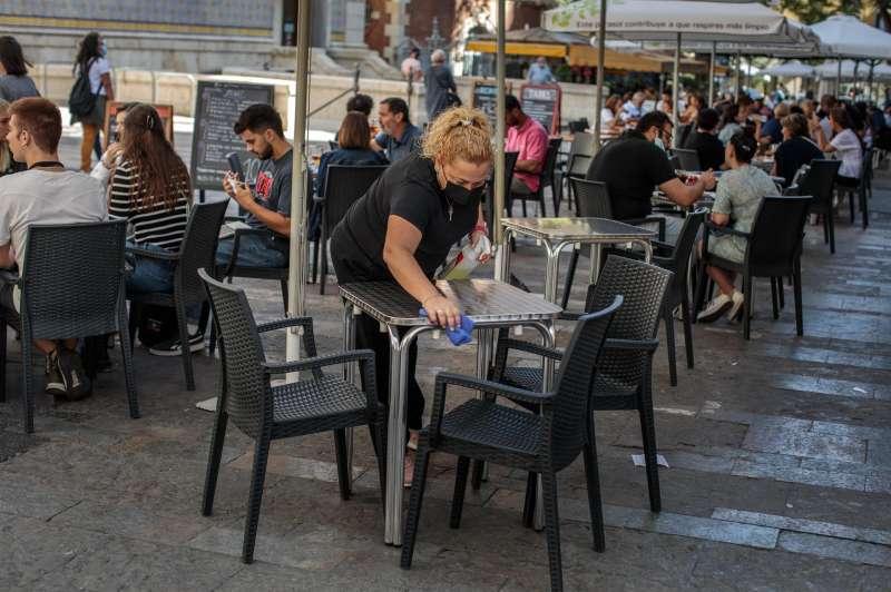 Una camarera desinfecta una mesa de una terraza en el centro de Valencia.