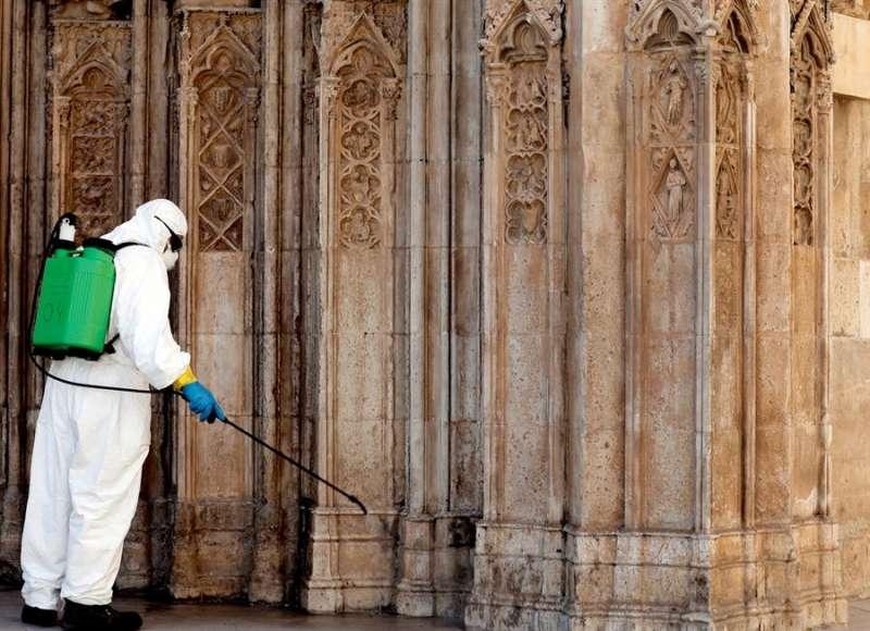 Un operario municipal con un equipo de protección individual ( EPI) desinfecta la puerta de los Apóstoles de la Catedral de Valencia.EFE/ Juan Carlos Cárdenas