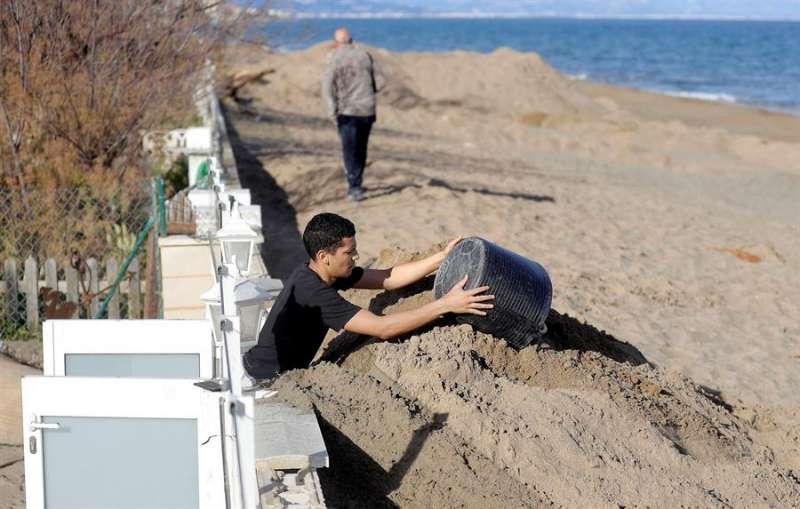 Un hombre retira los cerca de dos metros de arena que el temporal Gloria ha acumulado ante su vivienda. EFE