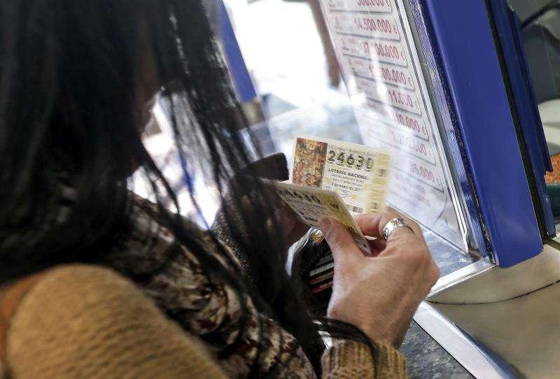 Una persona compra lotería en una administración de València. EFE/Archivo