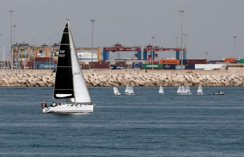 Un velero junto a un grupo de Óptimist navegan junto al puerto de Valencia este Sábado Santo, en el que las temperaturas han rondado los 25 grados.EFE/ Juan Carlos Cárdenas
