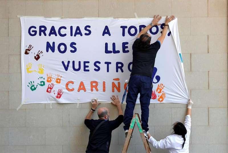 Trabajadores de una residencia de ancianos de Valencia, cuelgan una pancarta de agradecimiento a la población.EFE/ Manuel Bruque/Archivo