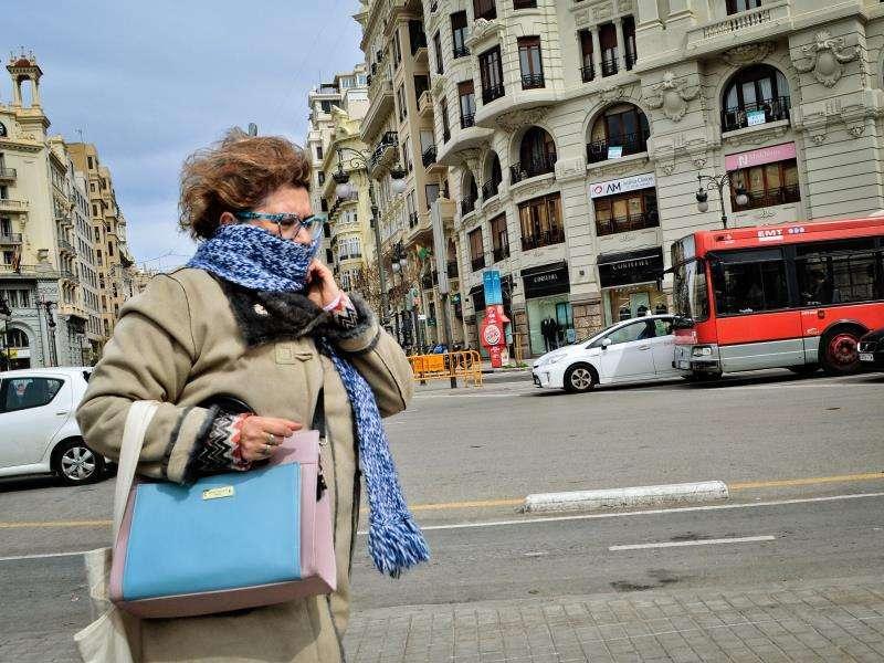 Una mujer se protege del viento y del frío en València. EFE/Archivo