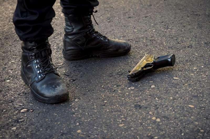 Un policía custodia la pistola tras el atraco a un banco. - EFE