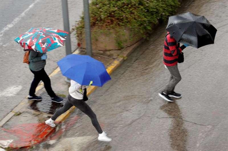 Tres personas se protegen con paraguas de la lluvia cuando, para este jueves. EFE/Kai Försterling