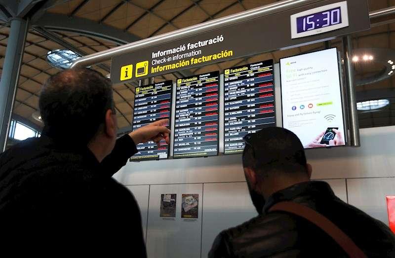Dos viajeros miran un panel tras el cierre por precaución a causa de la borrasca Gloria del aeropuerto de Alicante-Elche. EFE