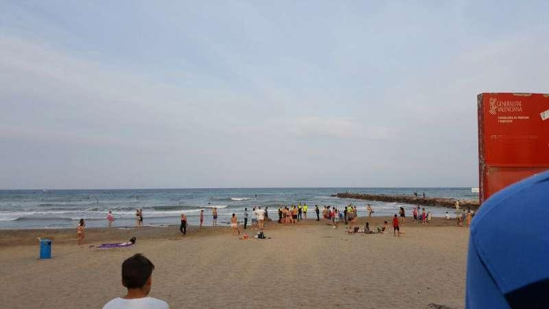 La policía con el fallecido en la playa de Port Saplaya. EPDA