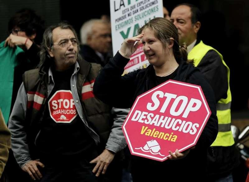 Miembros de la Plataforma de Afectados por la Hipoteca (PAH) tratando de evitar un desahucio. EFE/Juan Carlos Cárdenas