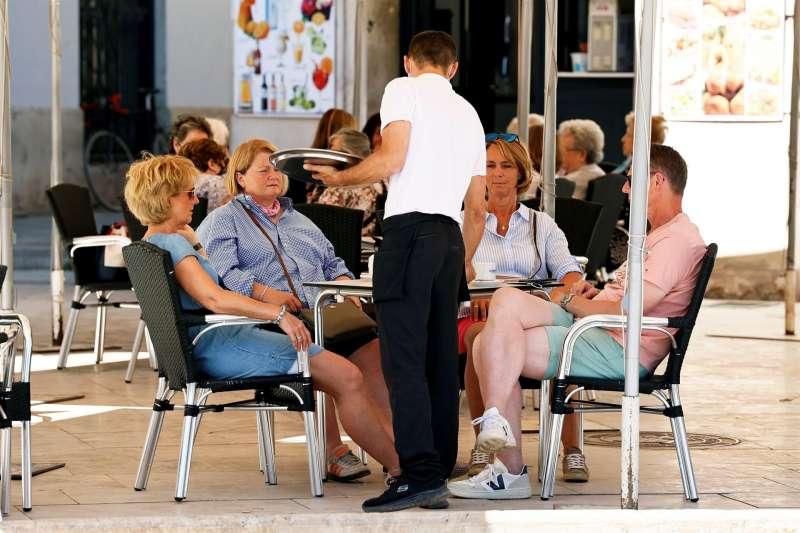 Turistas atendidos por un camarero en València.