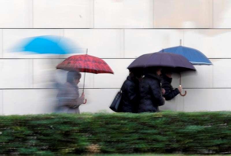Varias personas se protegen de la lluvia con paraguas. EFE/Kai Försterling/Archivo