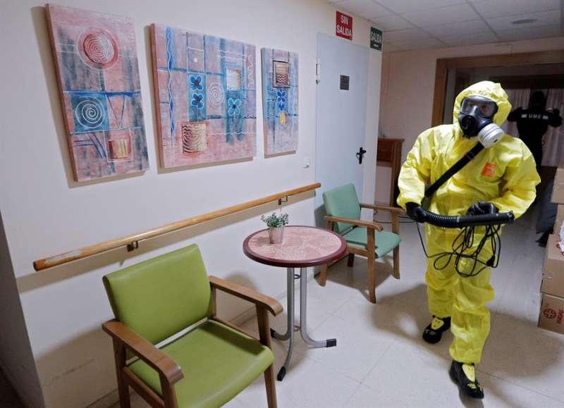 Un miembro del equipo GIETMA (Grupo de intervención en emergencias tecnológicas y medioambientales) de la UME (Unidad Militar de Emergencias) realiza labores de desinfección, como medida de prevención, en una residencia de ancianos. EFE/Kai Försterling/Archivo
