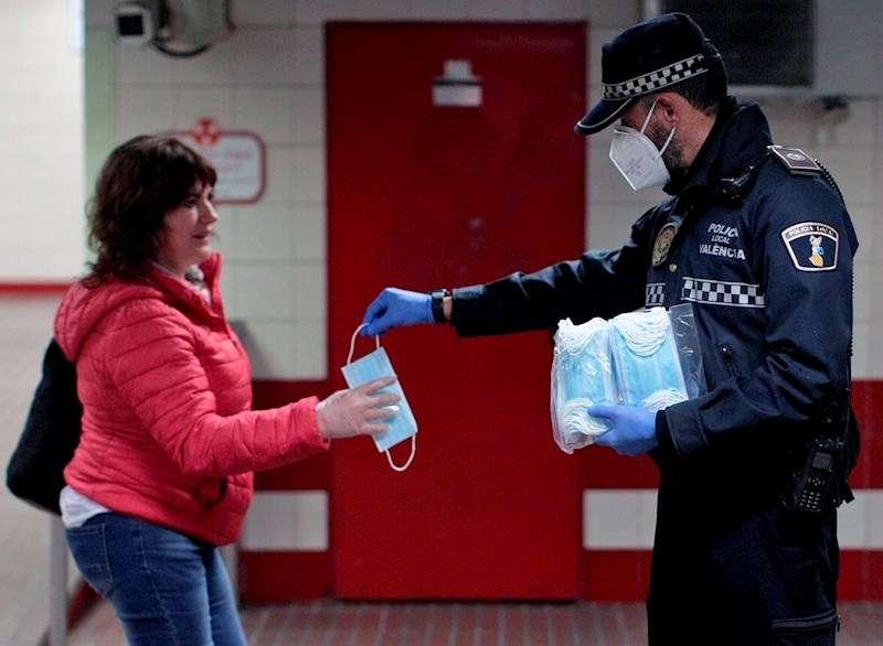 Un policía entrega una mascarilla a una viandante, en una imagen de esta semana. EFE
