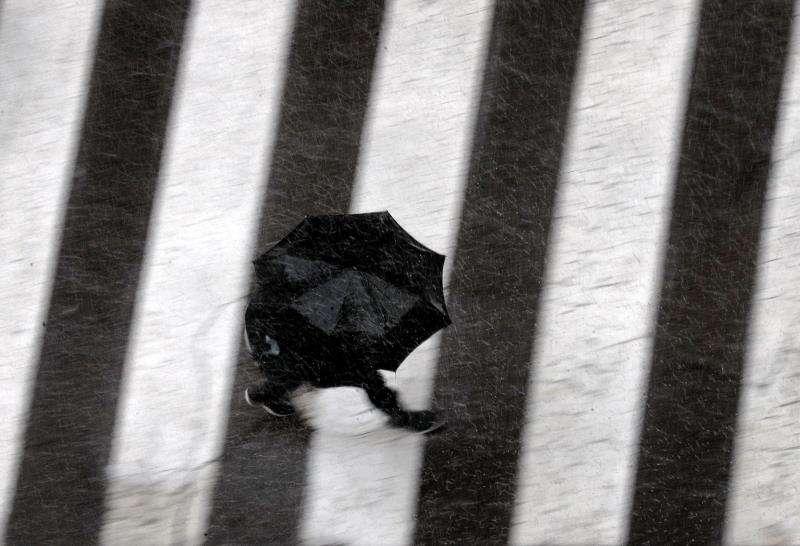 Una persona se protege de la lluvia con un paraguas. EFE