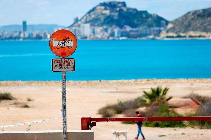 Un hombre pasea el perro ante una señal de prohibido el paso en la entrada a la playa de la Almadraba de Alicante. EFE