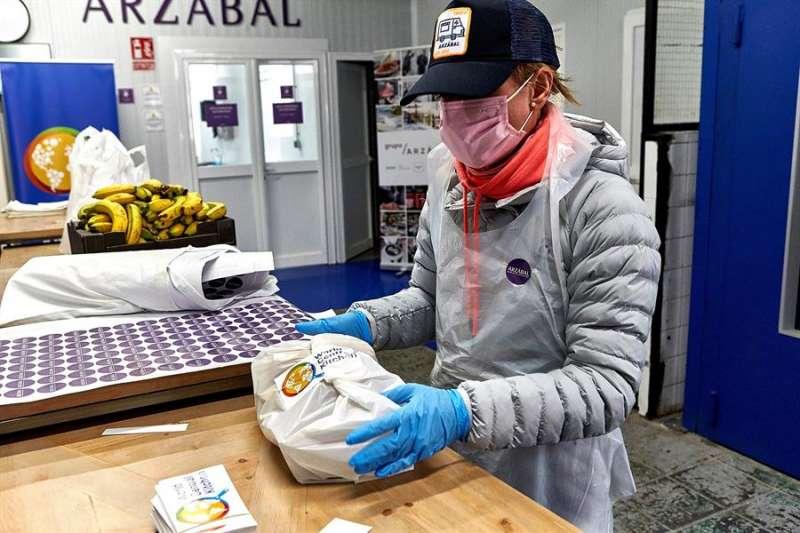 Una persona comprando en Valencia con guantes y mascarilla. EFE