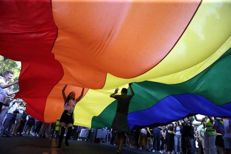 Dos personas caminan bajo una bandera arcoiris en una manifestación del Orgullo. EFE/Archivo