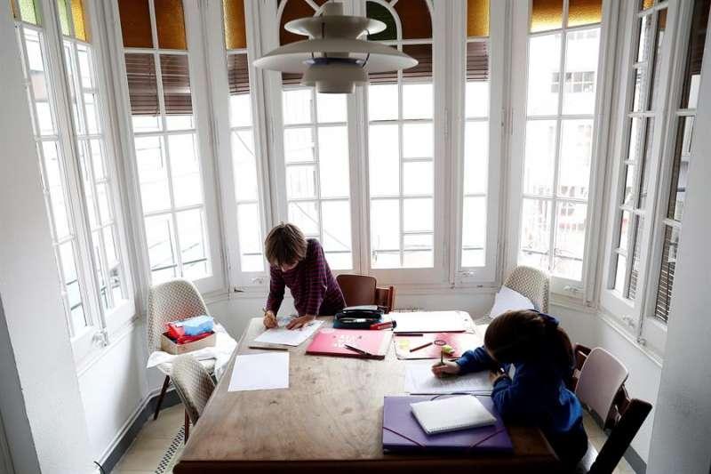 Dos niños hacen deberes en casa. EFE/Alberto Estévez/Archivo
