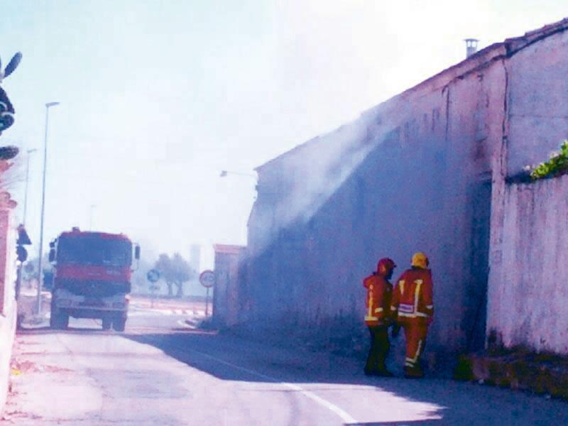 Dos bomberos frente a la antigua bodega que ardió y calcinó 6 vehículos que había en su interior. FOTO EPDA