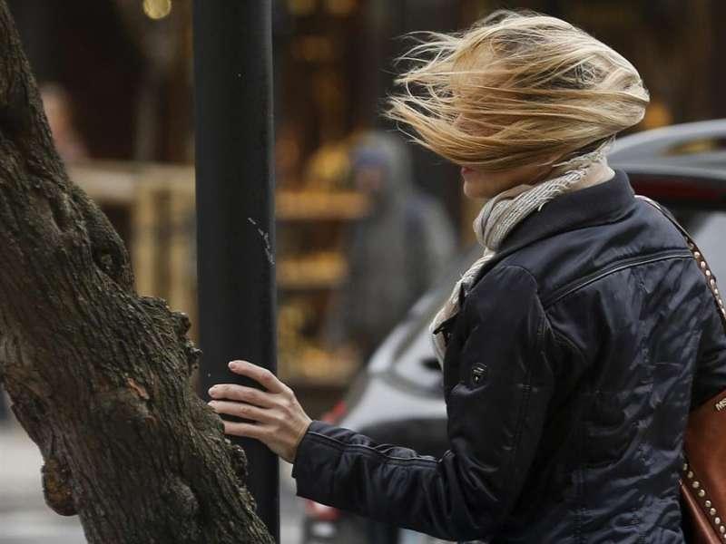 Imagen de archivo de una mujer que se sujeta en un semáforo a causa del viento. EFE/Javier Etxezarreta/Archivo