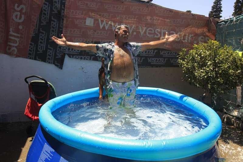 Un hombre se refresca en una piscina portátil instalada en el patio de su casa. EFE/Archivo