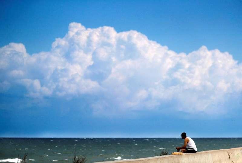Un hombre observa el mar desde el espigón de la Marina del Puerto de Valencia.