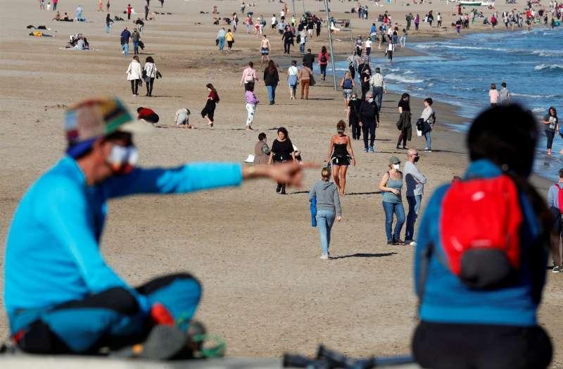 Numerosas personas en la playa de la Malvarrosa disfrutando de un día de otoño de buen tiempo.