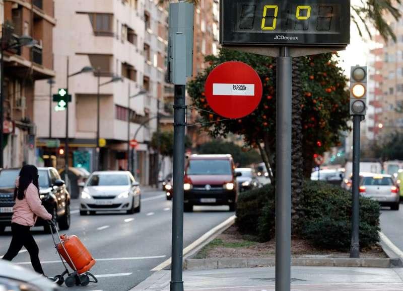 En la imagen, una joven transporta una botella de butano marcando el termómetro 0 grados a primeras horas de la mañana de este martes en el centro de la ciudad de València. EFE/ Juan Carlos Cárdenas