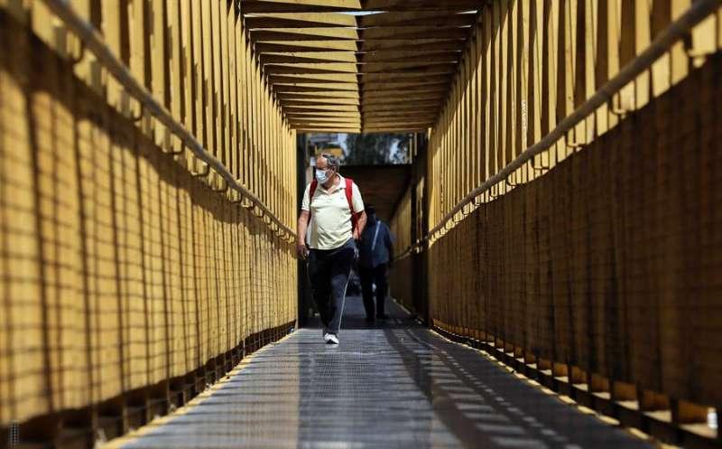 Imagen de archivo de una persona con mascarilla cruzando un puente en València. EFE