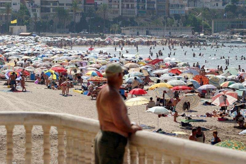 Un jubilado observa la gran cantidad de bañistas en la playa de Poniente de Benidorm. EFE/Archivo
