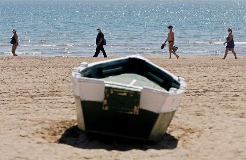 Cuatro personas disfrutan del buen tiempo y del calor en la playa de la Malvarrosa. EFE