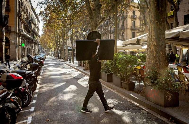Un camaerero monta una terraza en las Ramblas de Barcelona, con limitaciones de aforo y horario. EFE/Enric Fontcuberta