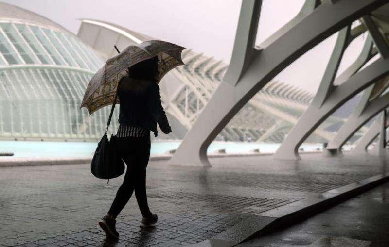 En la imagen, una persona se resguarda de la lluvia en la Ciudad de las Ciencias de València. EFE/Archivo