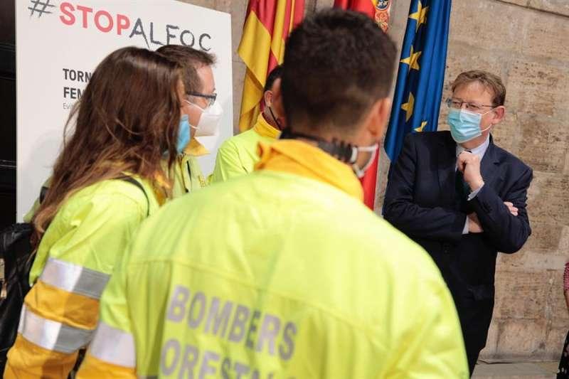 El president de la Generalitat, Ximo Puig (d), conversa con unos bomberos forestales durante la presentación este jueves del plan estratégico contra incendios