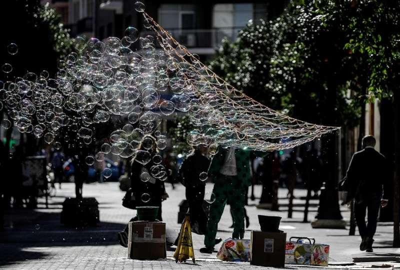 Un artista callejero exhibe sus pompas de jabón en la céntrica calle Ruzafa de Valéncia. EFE/ Manuel Bruque
