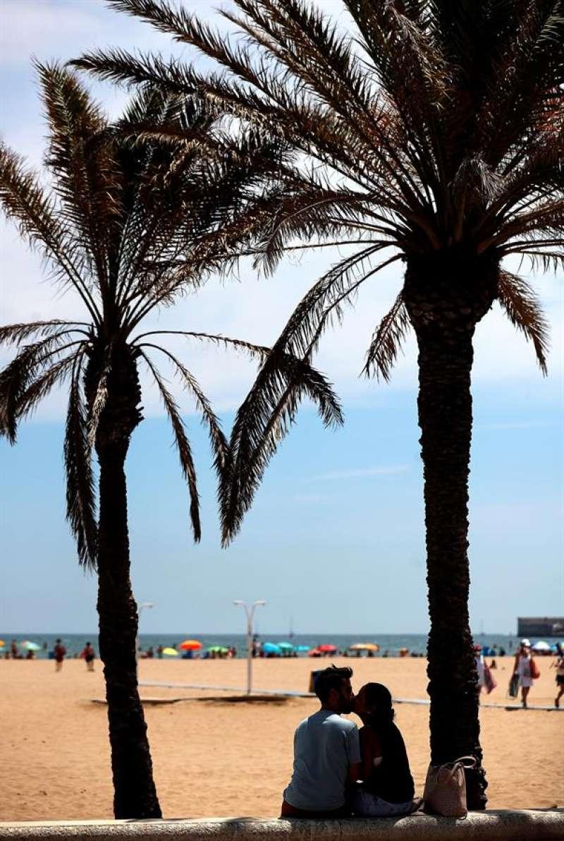 Una pareja se besa a la sombra de unas palmeras en la playa de Las Arenas de Valéncia, en un sábado marcado por el sol y las altas temperaturas. EFE/Manuel Bruque
