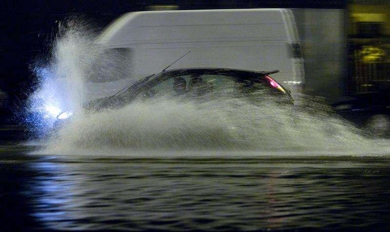 Un coche atraviesa una calle inundada a causa de una tromba de agua caída en València. EFE/Archivo