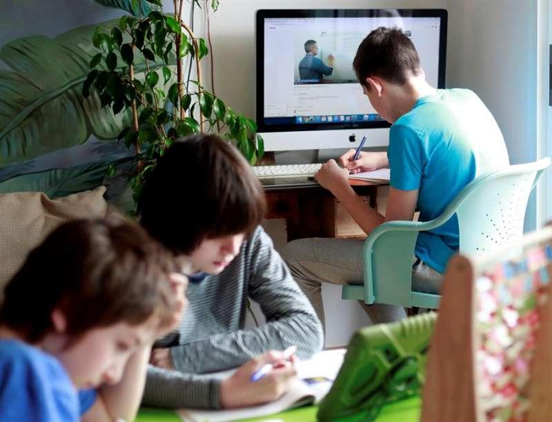 Tres menores realizan las tareas de clase de forma virtual en su casa. EFE/Xoán Rey/Archivo