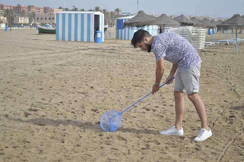 Un chico recoge las colillas de la arena. EPDA