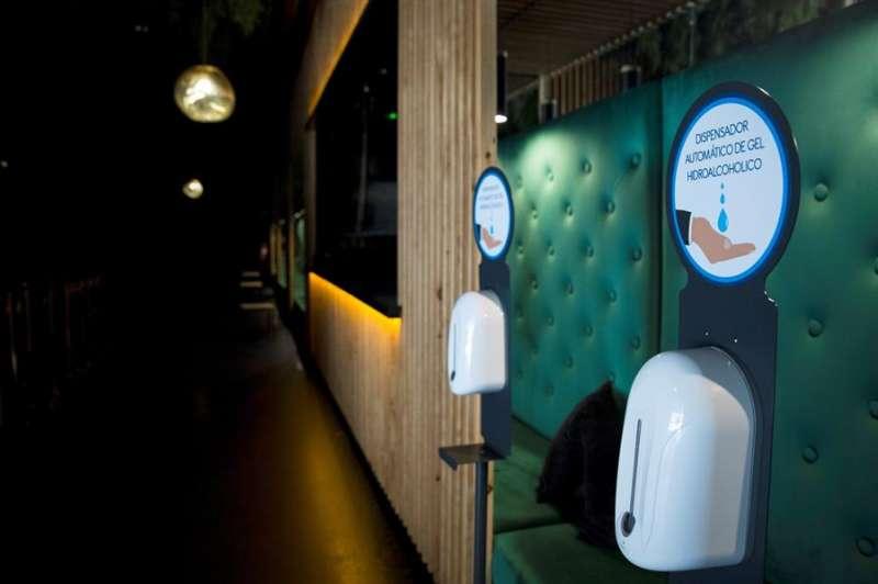 Gel hidroalcoholico y mamparas a la entrada de una discoteca en Madrid. EFE