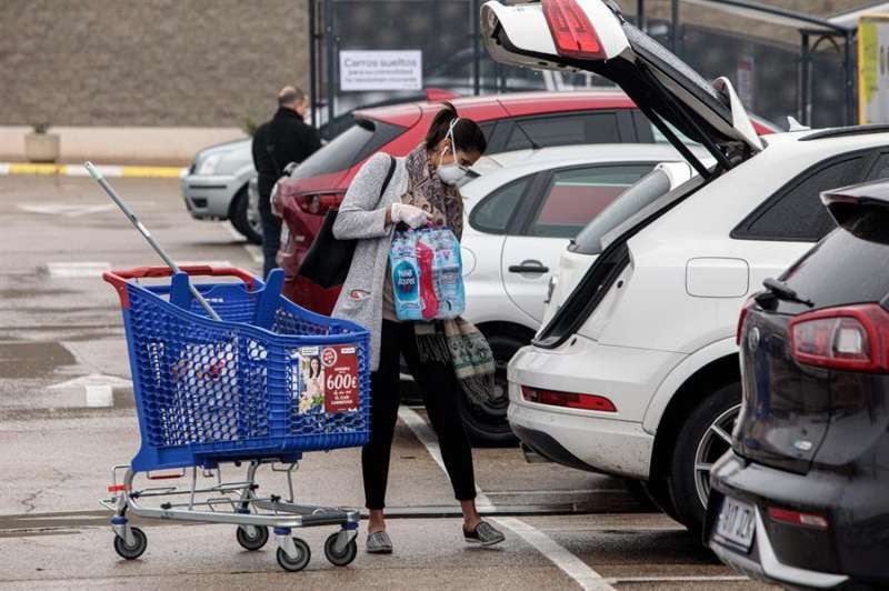 Una mujer guarda la compra con mascarilla. EPDA/Archivo