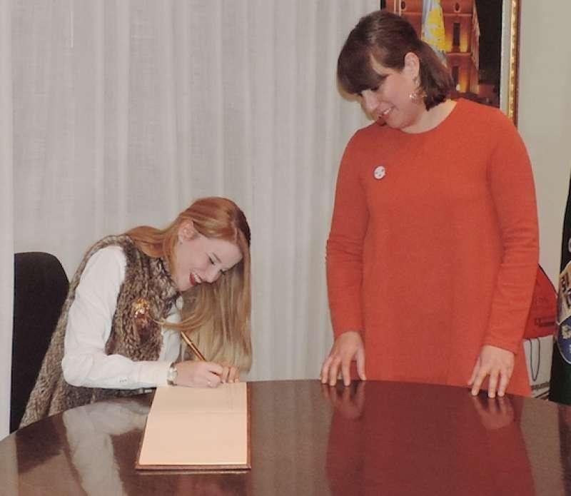 La FM de Bétera firmando en el libro de honor del Ayuntamiento junto a la alcadesa Cristina Alemany. //EPDA