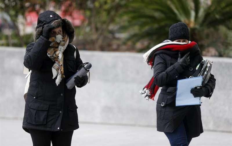 Dos mujeres se abrigan debido al frío y al viento. EFE