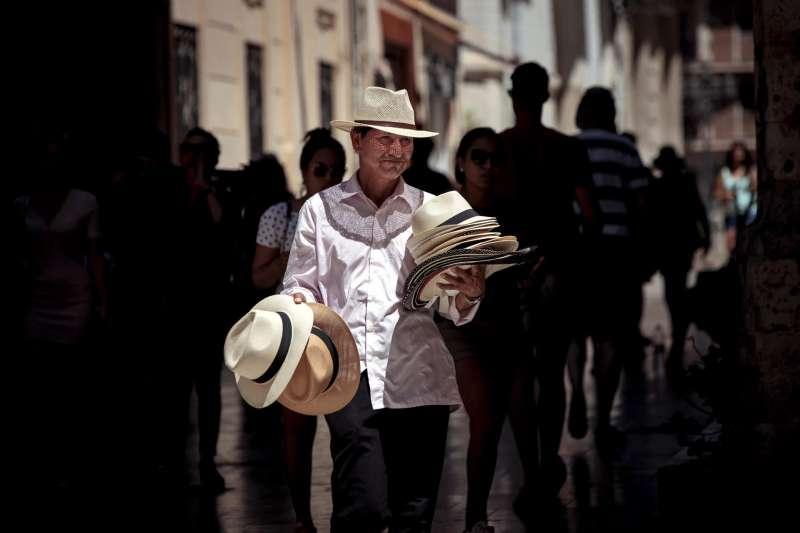 Un vendedor ambulante ofrece sombreros.